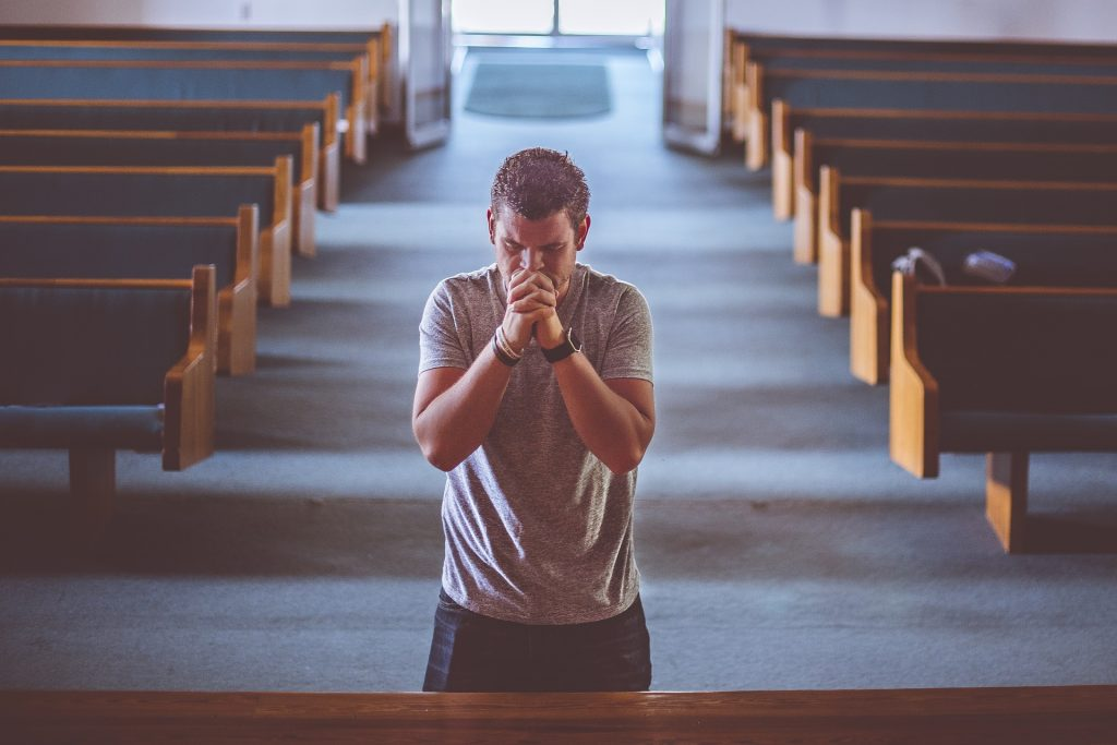 man praying empty pews